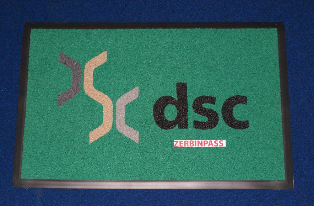 tappeto ricciolo vinilico articolo 1700 verde personalizzato ad intarsio con logo del cliente e rampa antinciampo in gomma