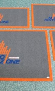 tappeti riccioolo vinilico grigio con bordo esterno arancio e personalizzazione ad intarsio blu milano ristorazione
