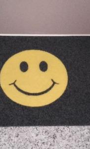 zerbino sintetico articolo 350 colore nero personalizzato con smile colore giallo posizionato davanti alla porta dell'appartamento (2)